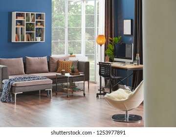 Modern room, blue wall, wooden desk and desktop room corner, sofa, frame carpet and furniture decor with lamp.