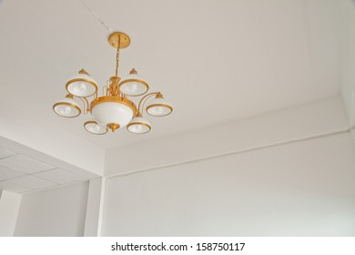 Modern room with chandelier ,  panel and white concrete wall