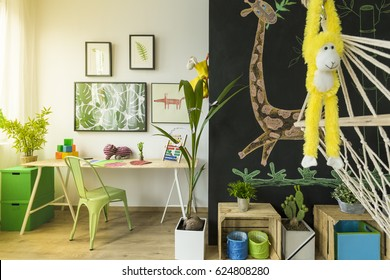 Modern room for children with hammock, monkey maskot and giraffe drawing on a wall