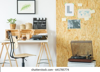 Modern room with desk, record player, posters and osb board