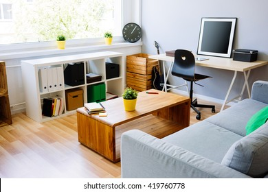 Modern room, home office interior. Room with sofa, desk, chair, small table and other furniture