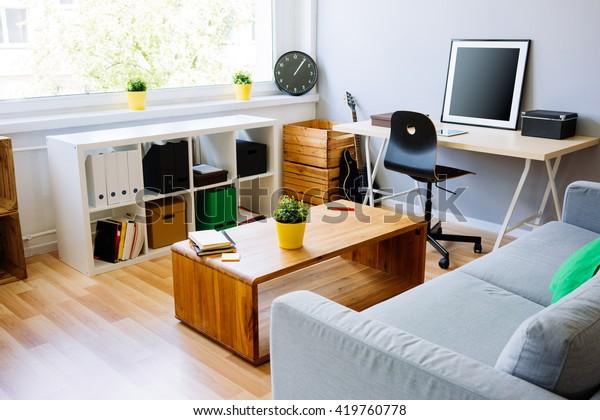 Modern oda, ev ofis iç. Kanepe, çalışma masası, sandalye, küçük masa ve diğer mobilyalarla donatılmış oda
