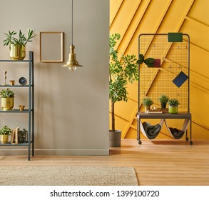 Modern room interior concept, grey bookshelf, gold lamp and frame close up, green metal chair with pillow and blanket style, brown and yellow decorative wall.