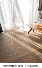 Modern room interior with an open window in minimal style. Transparent tulle with morning sun rays on shadow background. Vertical photo.