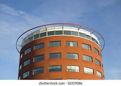 Modern round-shaped office building made of red brick and glass in Hoogvliet, Holland