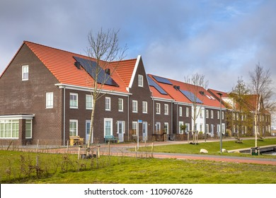 Modern row houses with solar panels, brown bricks and red roof tiles in Groningen Netherlands