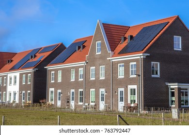 Modern row houses with solar panels, brown bricks and red roof tiles in neoclassical style in Groningen Netherlands on sunny day