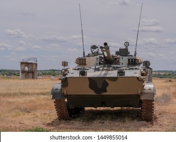 Modern Russian battle tanks near the destroyed city