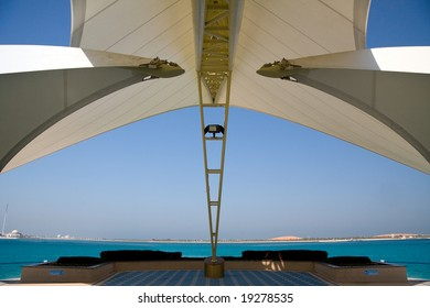 Modern sail like construction providing shade and framing a view of gulf and distant sand dunes