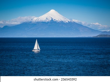 Modern sailboat sails in front of Osorno Volcano
