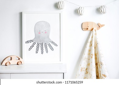 The modern sandinavian newborn baby room with mock up poster frame, wooden car, hanging towel and cotton lamps. Minimalistic and cozy interior with white walls.