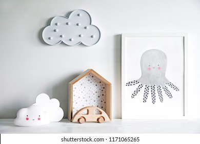 The modern sandinavian newborn baby room with mock up poster frame, wooden car and clouds. Minimalistic and cozy interior with white walls.