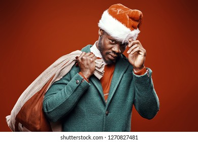 Modern Santa Claus. Smiling emotional man posing in green coat and red sweater, with santa hat and bag. Studio shot, red background