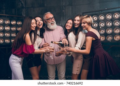 Modern Santa pours champagne into girl's glasses and smile. Happy Christmas day with fun group of attractive girls ad bearded man