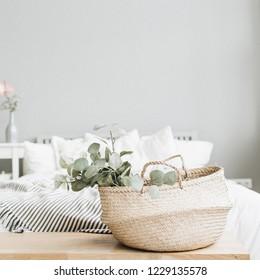 Modern scandinavian apartment interior design. Bed and eucalyptus branch.