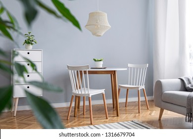 Modern scandinavian decor of living room with design furniture, family table, sofa and plants Brown wooden parquet and stylish carpet.  Nice and minimalistic apartment.