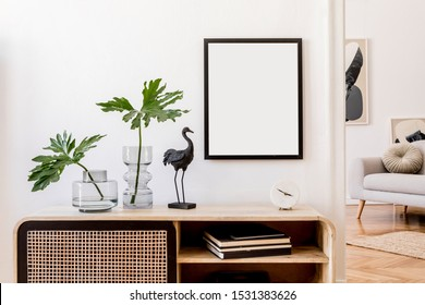 Modern scandinavian home interior with mock up photo frame, design wooden commode, black sculpture, tropical leaf, gray sofa and personal accessories. Stylish home decor. Template. Ready to use.