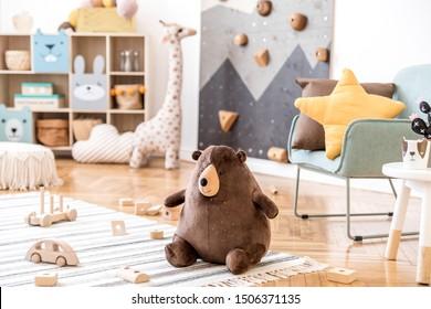 Décoration moderne scandinave de chambre d'enfant avec fauteuil à la menthe, mur d'escalade pour enfants, mobilier design, jouets doux, ours en peluche et accessoires pour enfants mignons. Décoration élégante de la salle de bains. Modèle.