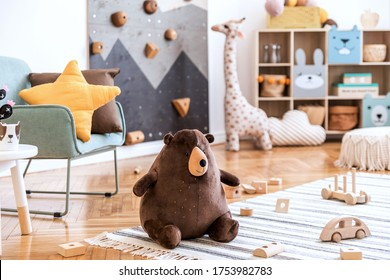 Modern scandinavian interior design of childroom with mint armchair, climbing wall for kids, design furnitures, soft toys, teddy bear and cute children's accessories. Stylish kidroom decor. Template.