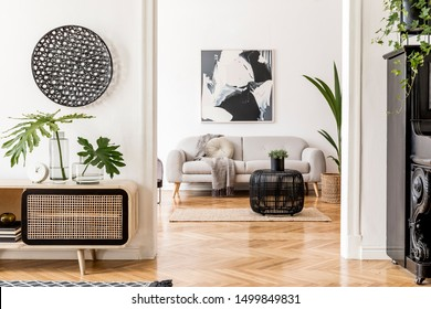 Modern scandinavian interior design of open space with stylish wooden commode, gray sofa, black piano, rattan table, plant, tropical leaf and elegant personal accessories. Stylish home decor. Template