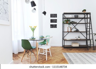 Modern scandinavian interior of living room with family table and lot of plants. White walls with mock up graphics project and brown wooden parquet.