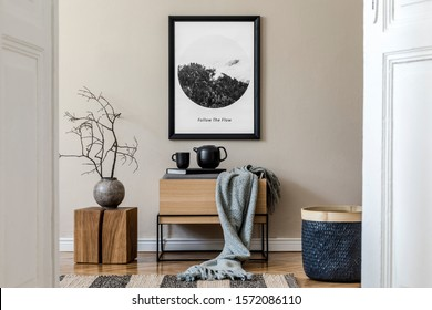 Modern scandinavian living room interior with black mock up poster frame, design commode,  leaf in vase, black rattan basket, books and elegant accessories. Template. Stylish home decor.  - Shutterstock ID 1572086110