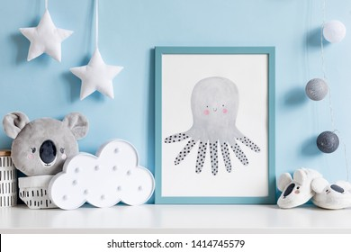 The modern scandinavian newborn baby room with mock up poster frame, koala bear, cloud and children accessories. Minimalistic and cozy interior with blue walls. Haniging cotton balls and stars