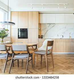 Modern scandinavian open space interior of kitchen with design furniture, black fridge, marble walls and brown wooden parquet. Elegant and floral accesories.