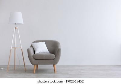 Modern scandinavian parlor or home office interior. Vintage gray armchair with white pillow, lamp on wooden floor, on light wall background in living room, flat lay, copy space, studio shot, mockup