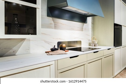 Modern Scandinavian-style kitchen interior with induction hob and large range hood