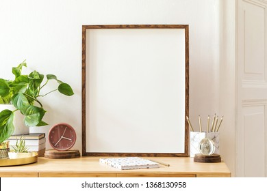 Modern scanidnavian interior with mock up photo frame, design office accessories and plants on the wooden desk. Beautiful mirror on the white wall. Creative desk of home decor. Warm and sunny room.