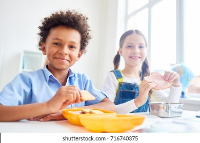 Modern schoolkids eating snacks from containers at break
