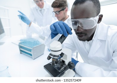 modern scientist uses a microscope in a laboratory