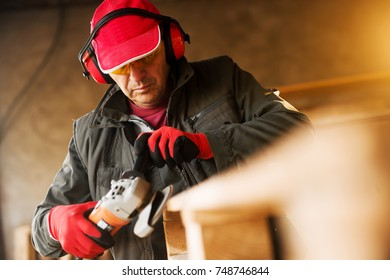 Modern senior fabric worker in a professional uniform and protection working with an electric grinder on a wood pallet.
