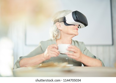 Modern senior female with virtual reality headset sitting by table and having tea or coffee