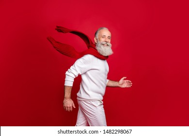 Modern senior man plays santa character at family party wearing fashion knitted clothes isolated red background