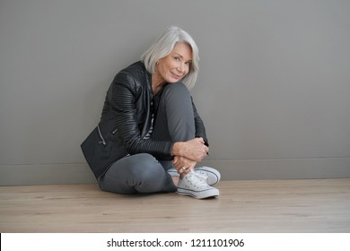 Modern senior woman sitting indoors with leather jacket