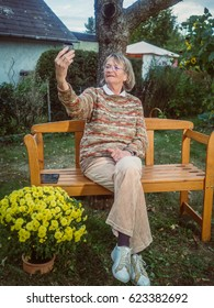 Modern senior woman is taking a selfie. She is sitting on a bench in her garden