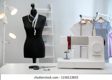 Modern sewing machine with tailor's supplies on table in workshop
