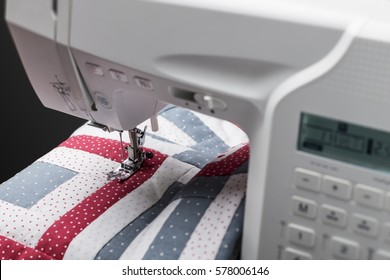Modern sewing machine working on a beautiful quilt