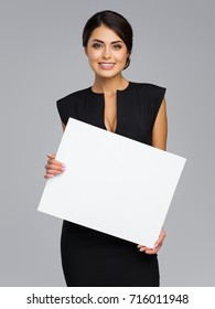 Modern and sexual business woman holds a banner of white color in hand. She is dressed in a strict black dress