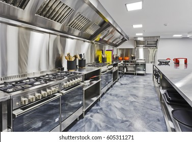 Modern shiny kitchen with stainless still kitchenware and equipment for restaurant-scale cooking with preparation tables, pans, pots, stoves.