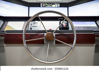 Modern ship control panel with steering wheel and engine accelerators on the captain bridge