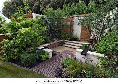 MODERN SHOW GARDEN WITH PLANTED BORDERS IN RAISED CONTAIERS. CHELSEA. LONDON. MAY  2010.  Design idea with planted raised borders with flowers, shrubs and paved enterance to building .