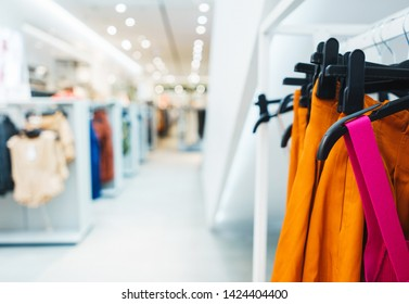 Modern show room selling clothes men, women and children. Hangers bright fashionable clothes. T-shirts, blouses and shirts on a hanger in the mall close-up. Soft focus, bokeh. Sell-out. Style.