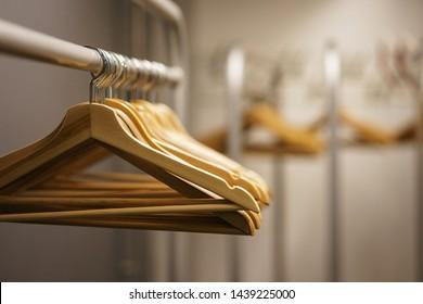 Moderner Showroom zum Verkauf von Kleidung für Männer, Frauen und Kinder. Leere Hänger in einem Mode-Laden. Kosmetikraum, Trachtenzubereitung. Mode-Show, saubere leere Raum für Kleidung vor der Veranstaltung.