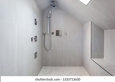 Modern shower with gray tiles steam shower, rain shower head and handheld shower head. With built-in seat and skylight