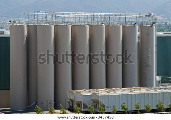 The modern silos of a manufacturing plant and the train's boxcars