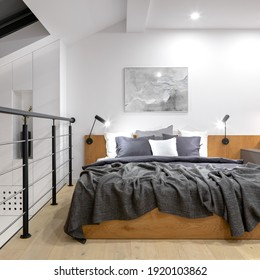 Modern and simple mezzanine bedroom with wooden and comfortable bed and balustrade