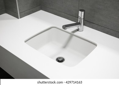 Modern sink made of artificial white stone, Contemporary minimalist washbasin with chrome batteries, Bathroom with modern sink
